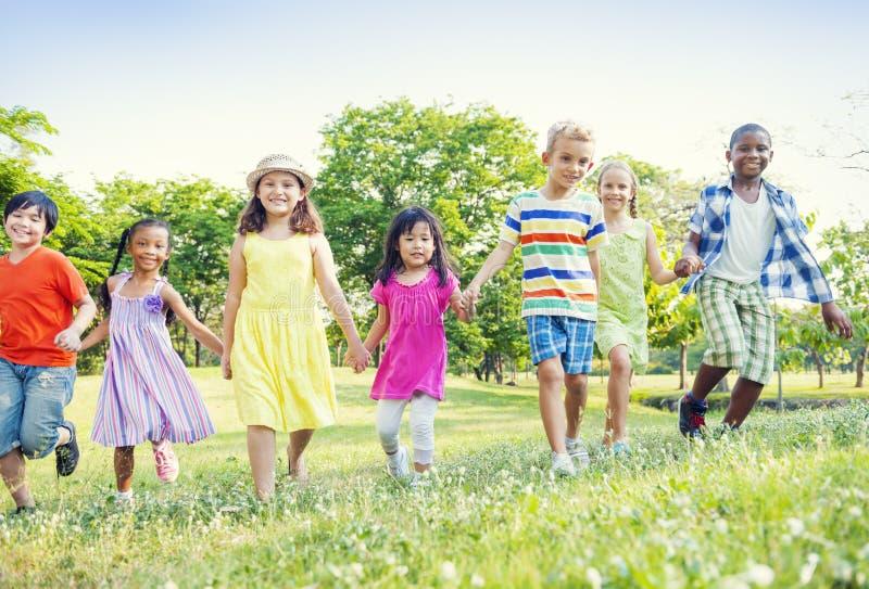 οι φίλοι παιδιών ομαδοποιούν το δέντρο πάρκων στοκ εικόνες