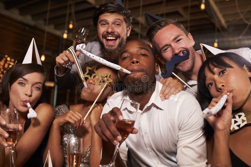 Οι φίλοι που έχουν τη διασκέδαση που γιορτάζει το νέο έτος σε έναν φραγμό, κλείνουν επάνω στοκ εικόνες
