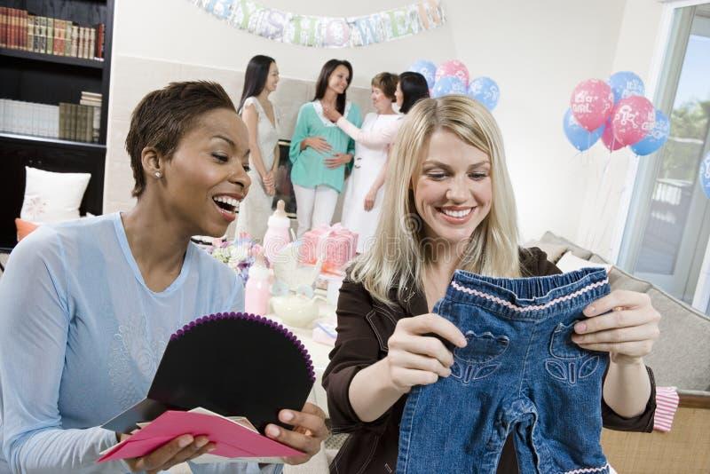 Οι φίλοι που εξετάζουν το μωρό πλημμυρίζουν τα δώρα στοκ φωτογραφία με δικαίωμα ελεύθερης χρήσης