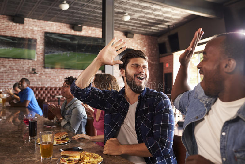 Οι φίλοι στο μετρητή στον αθλητικό φραγμό προσέχουν το παιχνίδι και γιορτάζουν στοκ εικόνες