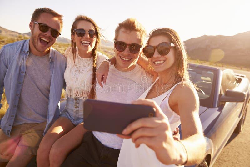 Οι φίλοι στο οδικό ταξίδι κάθονται στο μετατρέψιμο αυτοκίνητο που παίρνει Selfie στοκ φωτογραφία με δικαίωμα ελεύθερης χρήσης