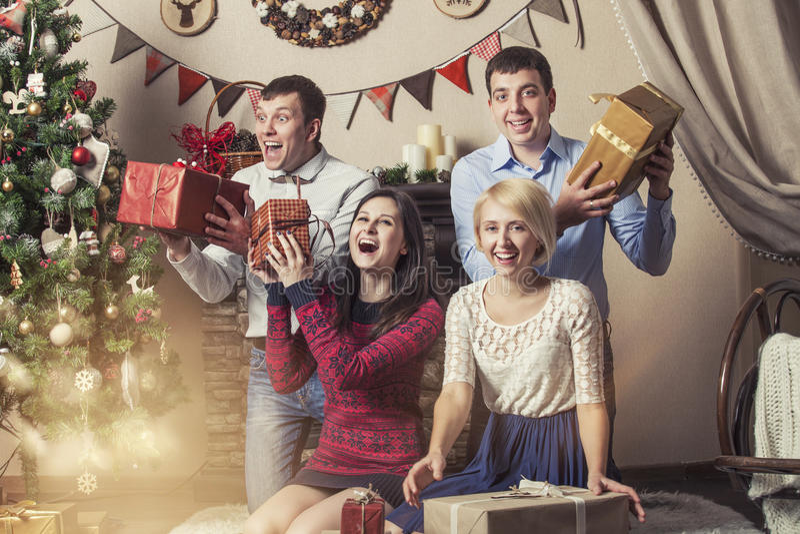 Οι φίλοι τεσσάρων ανδρών και γυναικών δίνουν τα δώρα στο interi Χριστουγέννων στοκ εικόνες