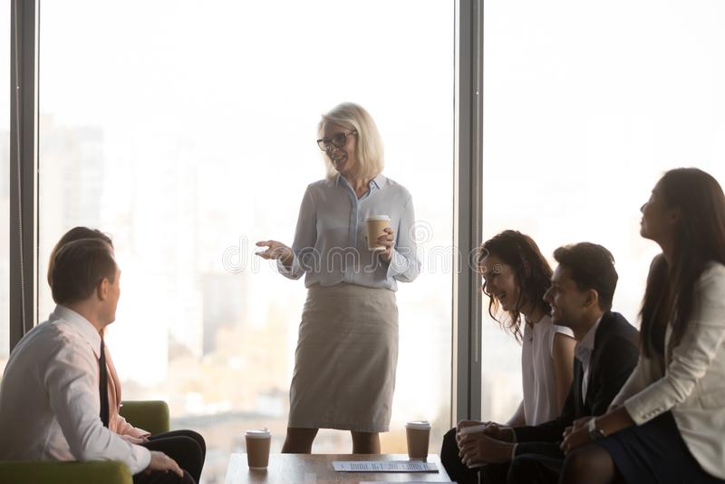 Οι φιλικοί εργαζόμενοι ομαδοποιούν και ο μέσος ηλικίας θηλυκός προϊστάμενος έχει τη συνομιλία διασκέδασης στοκ εικόνες