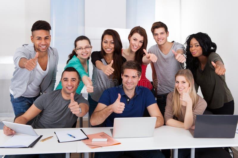 Οι φοιτητές πανεπιστημίου που οι αντίχειρες υπογράφουν επάνω από κοινού στοκ φωτογραφία με δικαίωμα ελεύθερης χρήσης
