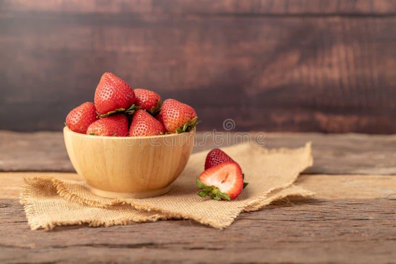Οι φράουλες είναι σε ένα ξύλινο μπολ σε ένα καφέ σακί στοκ εικόνα