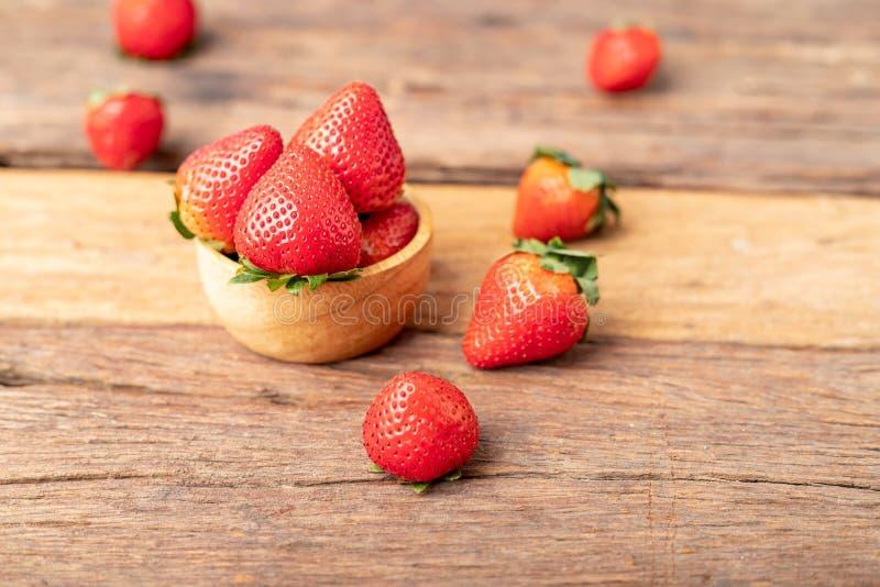 Οι φράουλες είναι σε ένα ξύλινο μπολ τοποθετημένο στο παλιό τραπέζι στοκ εικόνες