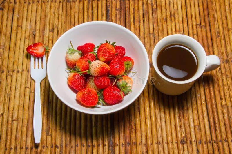 Οι φράουλες στο φλυτζάνι κύπελλων και καφέ, υπόβαθρο ινδικού καλάμου, επιλέγουν foc στοκ εικόνες