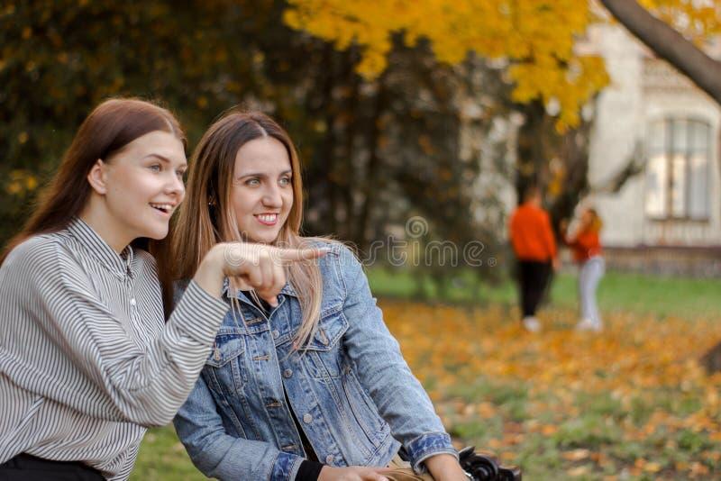 Οι χαριτωμένες φίλες παρατήρησαν κάτι μακριά σε έναν πάγκο στο πάρκο φθινοπώρου στοκ φωτογραφίες
