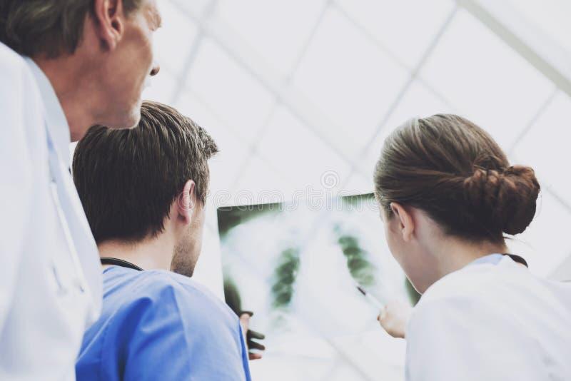 Οι χειρούργοι εξετάζουν προσεκτικά την ανίχνευση ακτίνας X στο νοσοκομείο στοκ φωτογραφίες