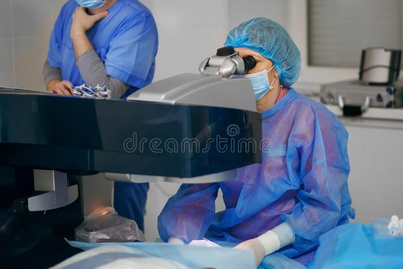 Οι χειρούργοι ματιών εκτελούν τη χειρουργική επέμβαση στον ασθενή χειρούργοι στην εργασία ιατρικές συλλήψεις στοκ εικόνα με δικαίωμα ελεύθερης χρήσης