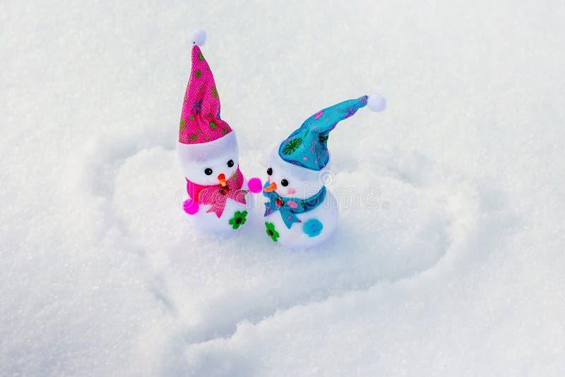 Οι χιονάνθρωποι παιχνιδιών είναι στο χιόνι στο οποίο η καρδιά είναι χρωματισμένη Συγχαρητήρια σε Day_ του βαλεντίνου στοκ εικόνες