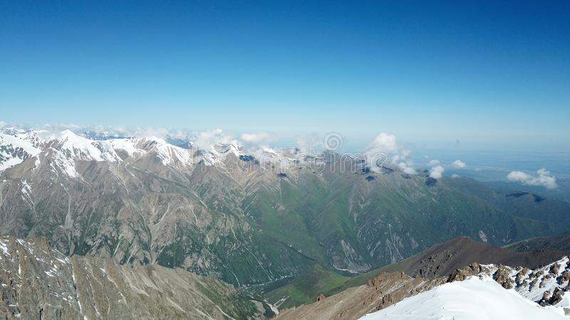 Οι χιονώδεις αιχμές των βουνών αυξάνονται επάνω από το μπλε ουρανό Ένας παγετώνας είναι ορατός στοκ φωτογραφίες