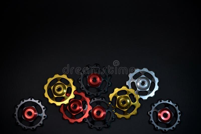 Οι χρωματισμένοι κύλινδροι, ο Μαύρος, κόκκινο, χρυσά εργαλεία για το ποδήλατο εκτρέφουν το derailleur που τοποθετείται χαοτικά στ στοκ φωτογραφίες με δικαίωμα ελεύθερης χρήσης