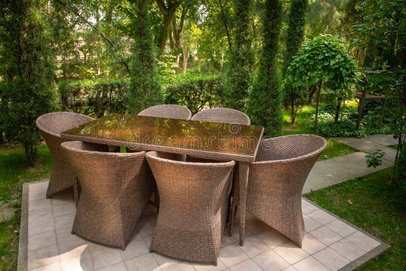 Οι ψάθινοι καρέκλες και ο πίνακας είναι στον κήπο κοντά στα δέντρα στοκ εικόνα
