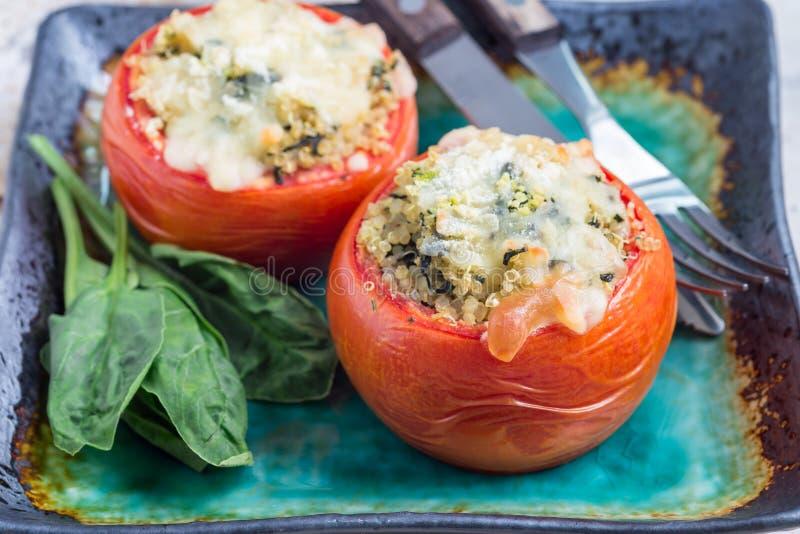 Οι ψημένες ντομάτες γέμισαν με quinoa και το σπανάκι που ολοκληρώθηκαν με το λειωμένο τυρί στο πιάτο, οριζόντιο στοκ εικόνες