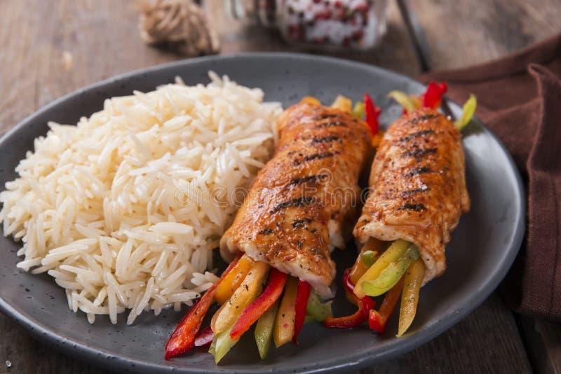 Οι ψημένοι στη σχάρα ρόλοι κοτόπουλου από τη λωρίδα κοτόπουλου γέμισαν τα γλυκά πιπέρια στοκ εικόνες