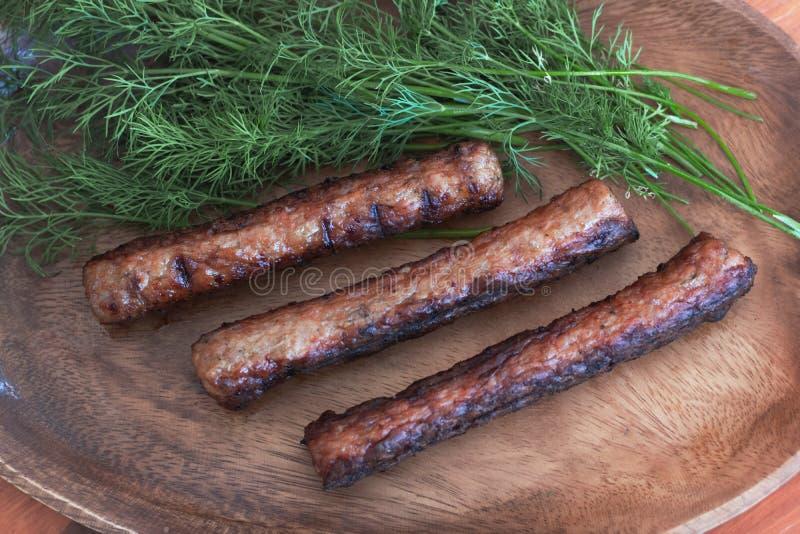 Οι ψημένοι στη σχάρα συνεταιρισμοί κρέατος εξυπηρετούνται σε ένα ξύλινο πιάτο με τα juicy πράσινα άνηθου στοκ φωτογραφίες με δικαίωμα ελεύθερης χρήσης