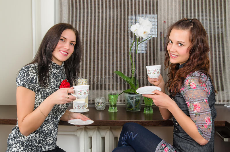 οι όμορφες γυναίκες πίνουν τα σπίτια τσαγιού και συνομιλίας στοκ φωτογραφία