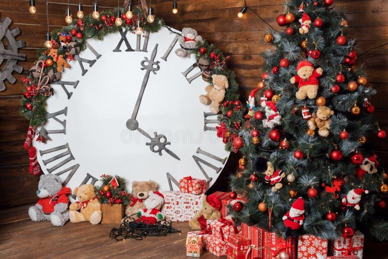 Οι όμορφες διακοπές διακόσμησαν το καθιστικό με το χριστουγεννιάτικο δέντρο και παρουσιάζουν Μεγάλο μαγικό ρολόι στον ξύλινο τοίχ στοκ εικόνα με δικαίωμα ελεύθερης χρήσης
