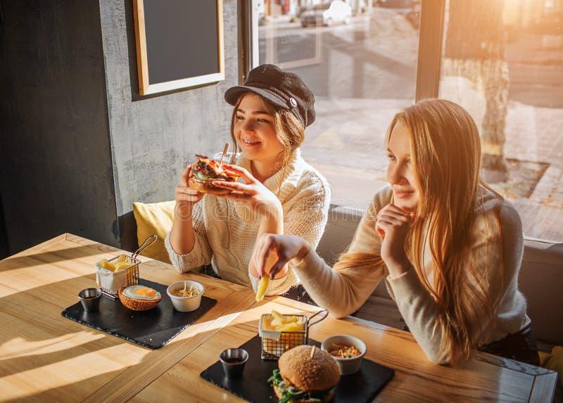 Οι όμορφες νέες γυναίκες κάθονται στον καφέ στον πίνακα Το Firls έχει burger στα χέρια Ένα άλλο κομμάτι λαβής της τηγανισμένης πα στοκ φωτογραφία
