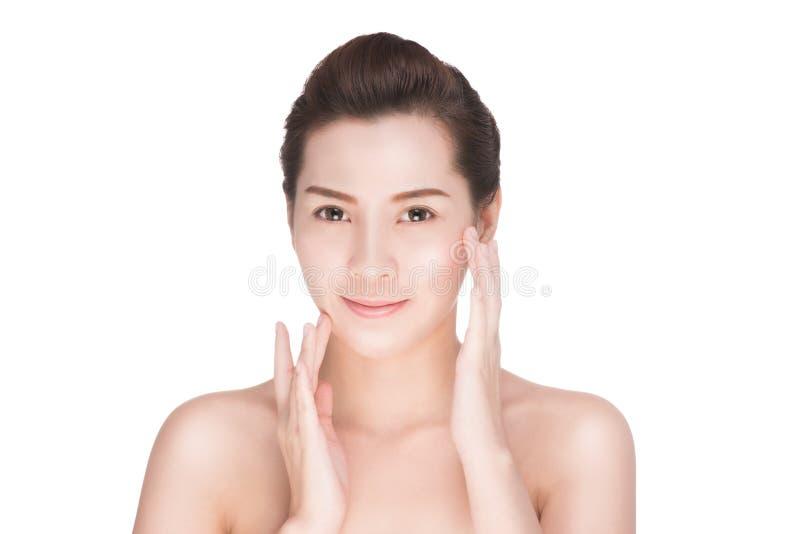 Οι όμορφες προσοχές γυναικών για το δέρμα αντιμετωπίζουν, ελκυστική ασιατική γυναίκα σχετικά με το πρόσωπό της στοκ φωτογραφία με δικαίωμα ελεύθερης χρήσης