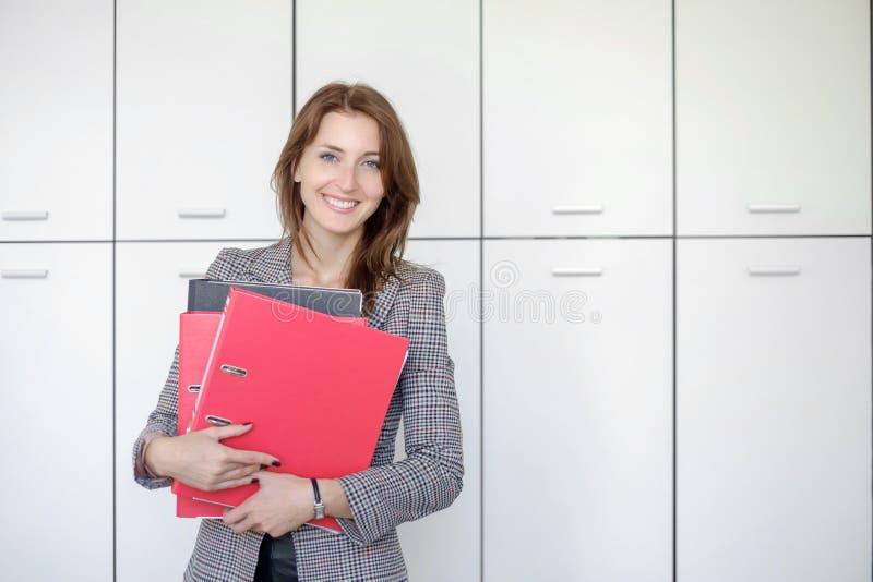 Οι όμορφες στάσεις επιχειρησιακών γυναικών με έναν κόκκινο φάκελλο παραδίδουν μέσα ένα γραφείο στοκ εικόνες