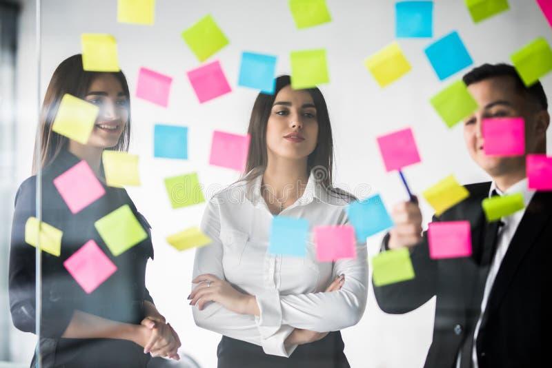 Οι όμορφοι επιχειρηματίες χρησιμοποιούν τις αυτοκόλλητες ετικέττες και το δείκτη, συζητούν τις ιδέες και χαμογελούν κατά τη διάρκ στοκ εικόνα