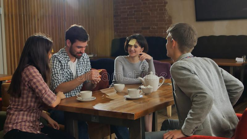 Οι όμορφοι νέοι παιχνίδι επιτραπέζιου στο παίζοντας ονόματος καφέδων με τις σημειώσεις αυτοκόλλητων ετικεττών στο μέτωπό τους στοκ φωτογραφία με δικαίωμα ελεύθερης χρήσης