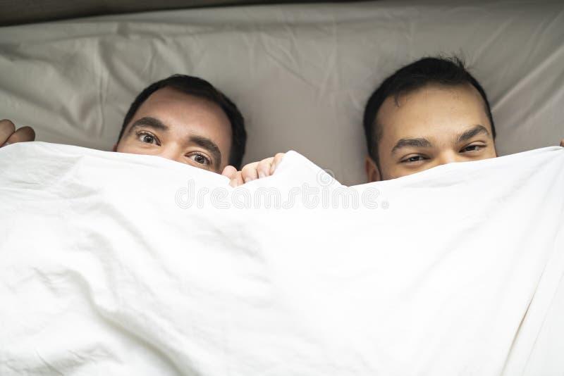 Οι όμορφοι ομοφυλόφιλοι συνδέουν στο κρεβάτι μαζί κάτω από την κάλυψη στοκ φωτογραφίες