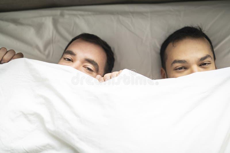 Οι όμορφοι ομοφυλόφιλοι συνδέουν στο κρεβάτι μαζί κάτω από την κάλυψη στοκ εικόνα