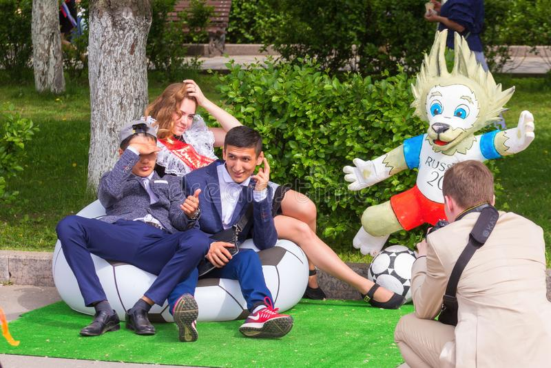 οι όμορφοι πτυχιούχοι νεαρών του σχολείου φωτογραφίζονται στο σύμβολο των τσεπών λύκων ποδοσφαίρου Παγκόσμιου Κυπέλλου, προετοιμα στοκ εικόνα