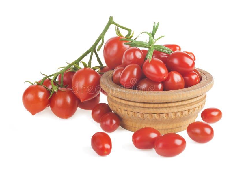 Οι ώριμες κόκκινες ντομάτες κερασιών διακλαδίζονται σε ένα ξύλινο πιάτο σε ένα άσπρο υπόβαθρο στοκ εικόνες