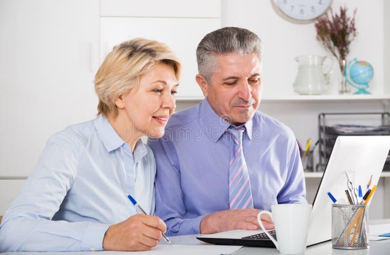 Οι ώριμοι υπάλληλοι εργάζονται με τα έγγραφα στοκ εικόνα με δικαίωμα ελεύθερης χρήσης