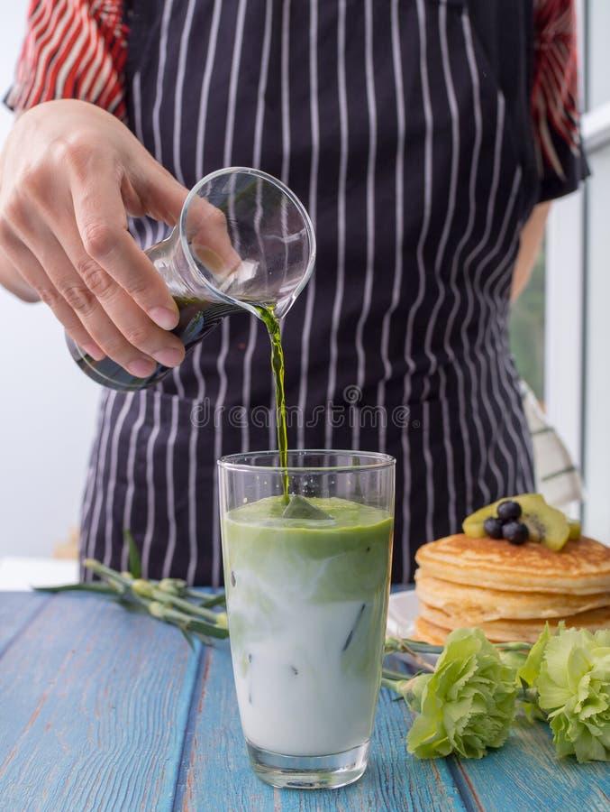Οι bartender γυναίκες χύνουν το πράσινο τσάι σε ένα ποτήρι του γάλακτος Το πράσινο τσάι τρώγεται με τις τηγανίτες Τσάι που αναμιγ στοκ φωτογραφία