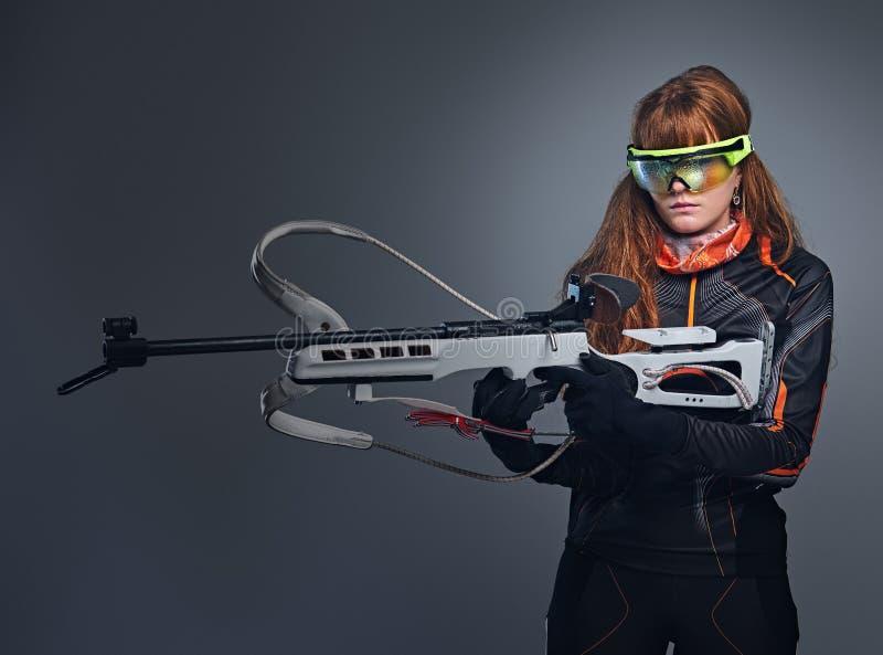 Οι Redhead θηλυκοί αθλητικοί τύποι Biatlon κρατούν το ανταγωνιστικό πυροβόλο όπλο στοκ εικόνα