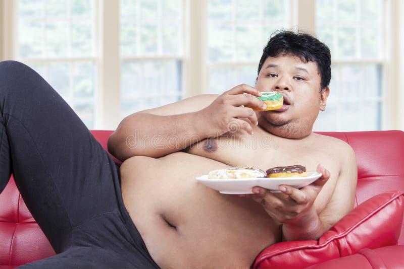 Οκνηρό παχύ πρόσωπο που τρώει donuts στοκ εικόνα