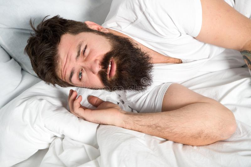 Οκνηρό πρωί Χαλαρώστε και έννοια ύπνου Γενειοφόρος ύπνος τύπων ατόμων στα άσπρα φύλλα Υγιείς ύπνος και ευημερία Άτομο γενειοφόρο στοκ φωτογραφίες