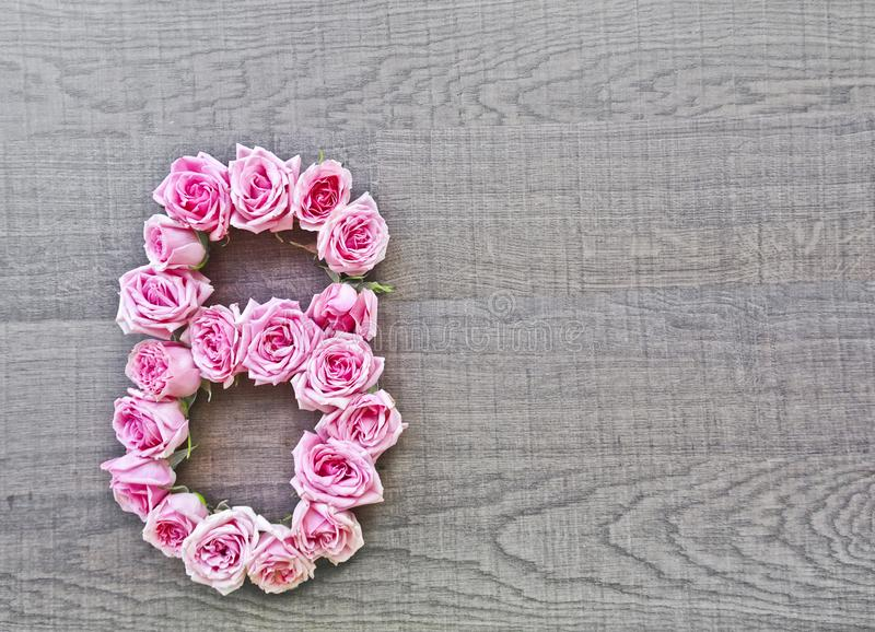 8, οκτώ - εκλεκτής ποιότητας αριθμός ρόδινων τριαντάφυλλων στο υπόβαθρο του σκοτεινού ξύλου στοκ φωτογραφία