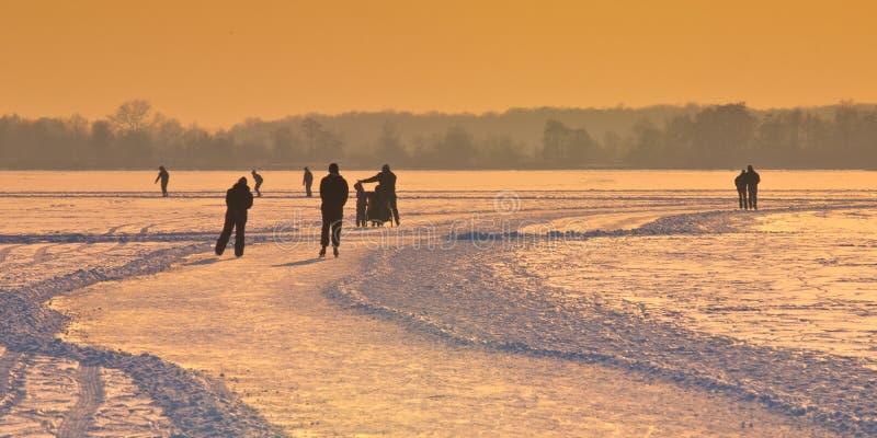 Ολλανδικοί σκέιτερ πάγου κάτω από τον ήλιο ρύθμισης στοκ εικόνα με δικαίωμα ελεύθερης χρήσης