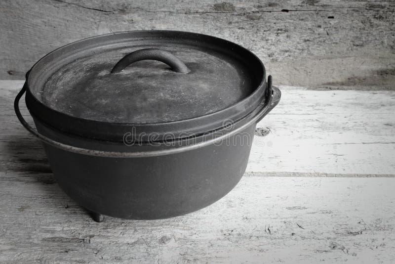 Ολλανδικός φούρνος χυτοσιδήρου με το παλαιό ξύλινο υπόβαθρο στοκ εικόνα