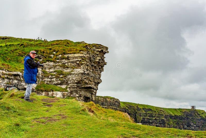 Ολλανδικός φωτογράφος με τη μπλε ζακέτα με τη κάμερα του κοντά στους απότομους βράχους Moher στοκ φωτογραφία