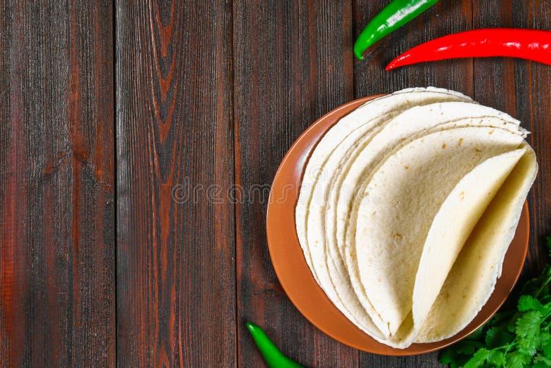 Ολόκληρα tortillas σίτου στον ξύλινους πίνακα και τα λαχανικά στοκ εικόνες