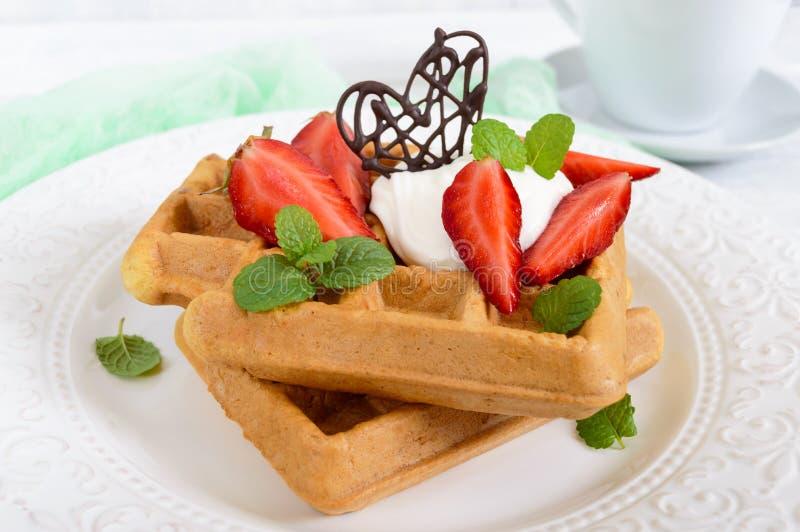 Ολόκληρες βελγικές βάφλες σίτου με την κτυπημένη κρέμα, πρόσφατα τεμαχισμένες φράουλες, φύλλα και σοκολάτα μεντών και ένα φλυτζάν στοκ εικόνα με δικαίωμα ελεύθερης χρήσης