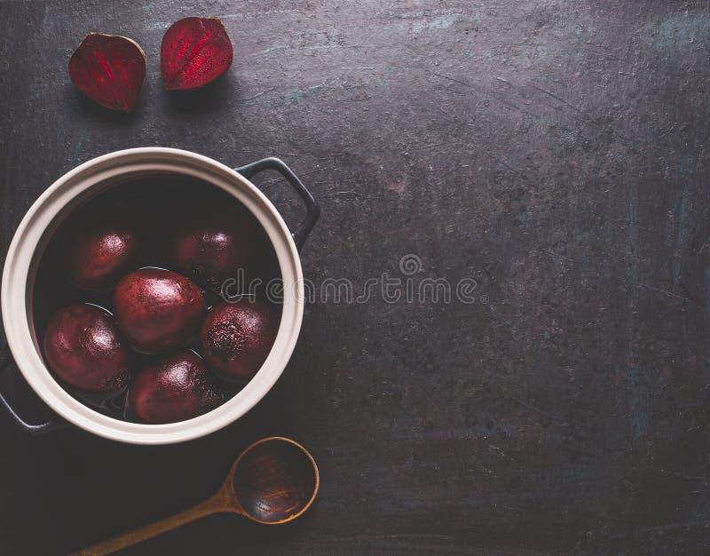 Ολόκληρες βρασμένες ρίζες τεύτλων στο μαγείρεμα του δοχείου με το ξύλινο κουτάλι στο σκοτεινό υπόβαθρο, τη τοπ άποψη με το διάστη στοκ εικόνες