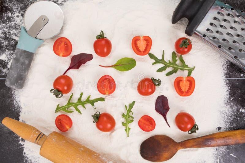 Ολόκληρες και διχοτομημένες ντομάτες στο αλεύρι, το arugula και το βασιλικό στοκ εικόνες