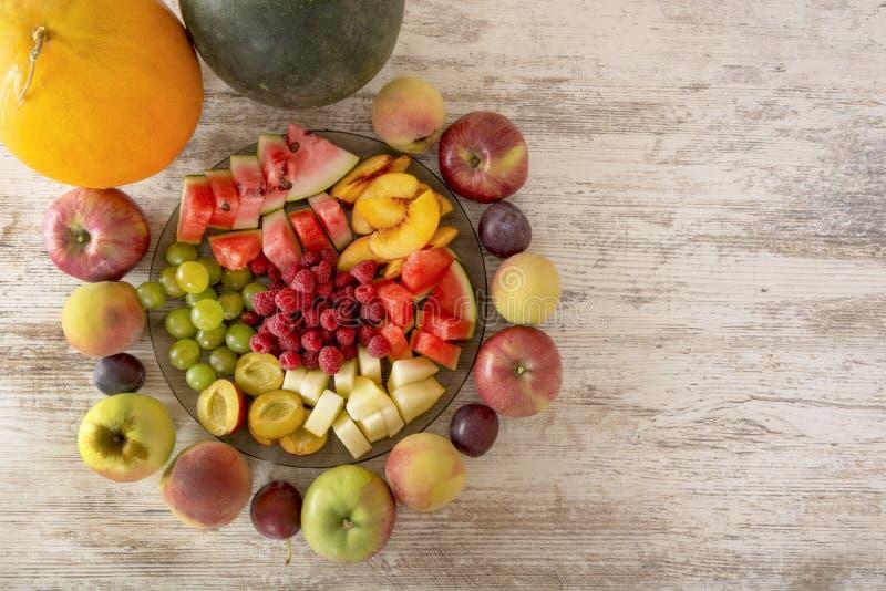Ολόκληρες τα φρούτα και οι φέτες σε ένα πιάτο βρίσκονται σε ένα άσπρο ξύλινο υπόβαθρο Επίπεδος βάλτε, αντιγράψτε το διάστημα στοκ εικόνες με δικαίωμα ελεύθερης χρήσης