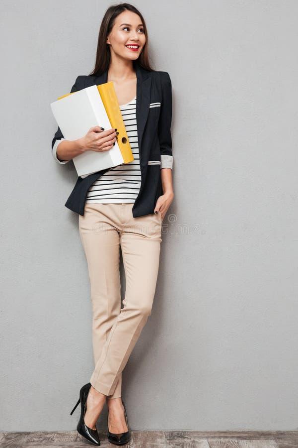 Ολόκληρη εικόνα της χαμογελώντας επιχειρησιακής γυναίκας με το βραχίονα στην τσέπη στοκ εικόνα