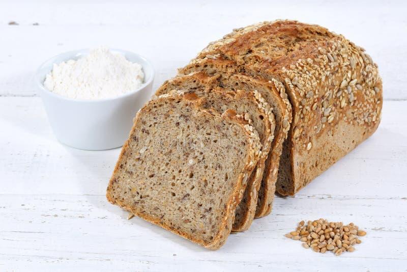 Ολόκληρη η φέτα ψωμιού σιταριού σίτου τεμαχίζει την τεμαχισμένη φραντζόλα στον ξύλινο πίνακα στοκ εικόνες με δικαίωμα ελεύθερης χρήσης