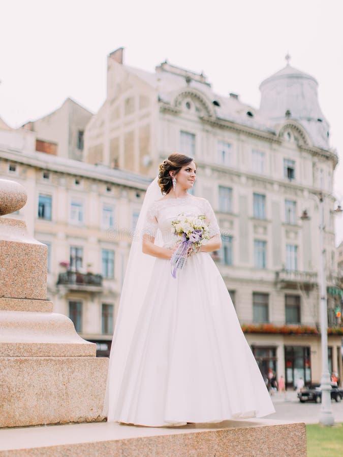Ολόκληρη φωτογραφία της ευτυχούς νύφης που κοιτάζει κατά μέρος στεμένος στα σκαλοπάτια στοκ εικόνες
