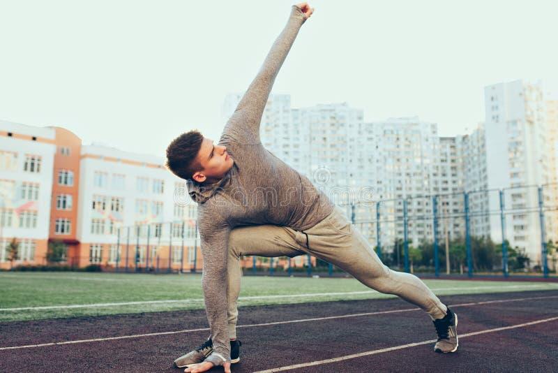 Ολόκληρη φωτογραφία του νέου τύπου στο workout το πρωί στο στάδιο Φορά το γκρίζο αθλητικό κοστούμι Κάνει την άσκηση στοκ εικόνα
